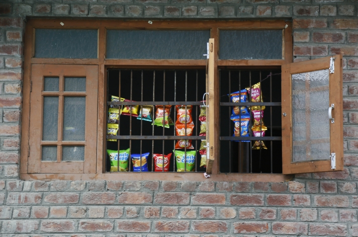 Snacks are displayed for sale by the window of a residential building as shops remain closed in Srinagar, Indian controlled Kashmir, Wednesday, Aug. 28, 2019. India's government, led by the Hindu nationalist Bharatiya Janata Party, imposed a security lockdown and communications blackout in Muslim-majority Kashmir to avoid a violent reaction to the Aug. 5 decision to downgrade the region's autonomy. The restrictions have been eased slowly, with some businesses reopening, some landline phone service restored and some grade schools holding classes again, though student and teacher attendance has been sparse. (AP Photo/Mukhtar Khan)