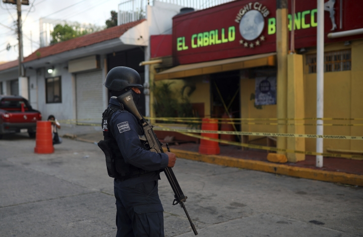 "A police officer guards the scene outside a bar where more than 20 people died in an overnight attack, in Coatzacoalcos, Mexico, early Wednesday, Aug. 28, 2019. President Andres Manuel Lopez Obrador said Wednesday ""the criminals went in, closed the doors, the emergency exits, and set fire to the place."" (AP Photo/Felix Marquez)"