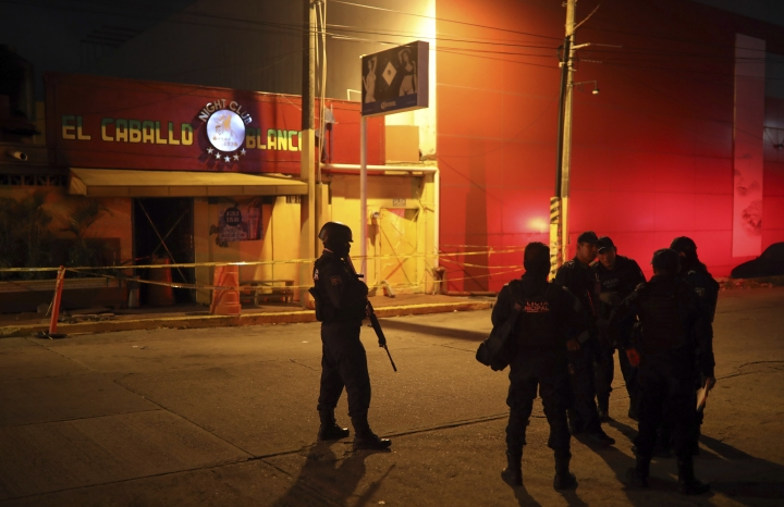 """Police officers guard the scene outside a bar where more than 20 people died in an overnight attack, in Coatzacoalcos, Mexico, early Wednesday, Aug. 28, 2019. President Andres Manuel Lopez Obrador said Wednesday """"the criminals went in, closed the doors, the emergency exits, and set fire to the place."""" (AP Photo/Felix Marquez)"""