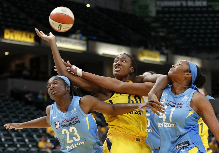 "FILE - In this May 7, 2018, file photo, Indiana Fever center Kayla Alexander, center, reaches for a rebound between Chicago Sky's Linnae Harper (23) and Alaina Coates (41) during the second half of a WNBA preseason basketball game in Indianapolis. Alexander has always loved to draw since she was a child, when she was inspired by a patient teacher. She continued to blossom as an artist as she grew up, attending art camps at the encouragement of her mom. Then basketball entered her life, earning her a scholarship to Syracuse before she went on to play in the WNBA and overseas. Now the 28-year-old Canadian has been able to combine her two loves, writing and illustrating a children's book, ""The Magic of Basketball,"" to be released Thursday, Aug. 29. (Matt Kryger/The Indianapolis Star via AP, File)"