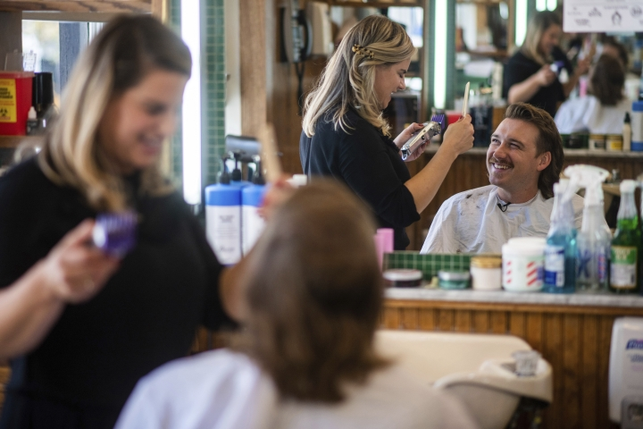 """Country singer Morgan Wallen receives a mullet at Paul Mole Barber Shop on Tuesday, Aug. 27, 2019, in New York. Wallen, who has turned heads with his likable hit song """"Whiskey Glasses,"""" said he decided to try a mullet after seeing old photos of his dad proudly rocking the hairstyle. (Photo by Charles Sykes/Invision/AP)"""