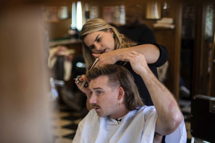 "Country singer Morgan Wallen receives a mullet at Paul Mole Barber Shop on Tuesday, Aug. 27, 2019, in New York. Wallen, who has turned heads with his likable hit song ""Whiskey Glasses,"" said he decided to try a mullet after seeing old photos of his dad proudly rocking the hairstyle. (Photo by Charles Sykes/Invision/AP)"