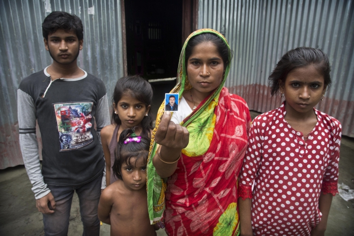In this Aug. 28, 2019, photo, Halimun Nessa, 32, stands with her children and displays a photograph of her husband Rahim Ali, who committed suicide the day before his children were to appear in front of a National Register of Citizens tribunal, in Barpeta, in India's northeastern state of Assam. Nessa said that her husband was worried their children would be excluded from a government citizenship list. India on Saturday, Aug. 31 plans to publish a controversial citizenship list that advocates say will help rectify decades of unchecked illegal immigration into the northeastern state of Assam from Bangladesh. Critics of the government's plan to publish a National Register of Citizens, fear it will leave off millions of people, rendering them stateless. (AP Photo/Anupam Nath)