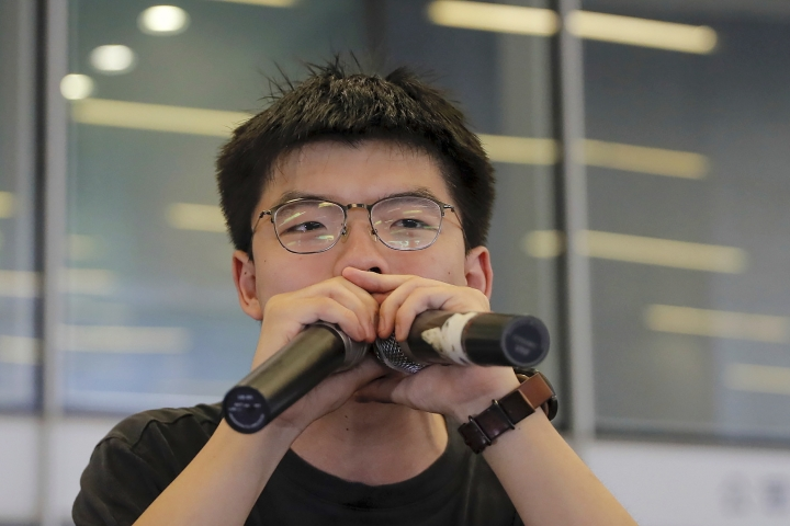 FILE - In this June 17, 2019, file photo, pro-democracy activist Joshua Wong speaks to protesters near the Legislative Council following a massive protest against the unpopular extradition bill in Hong Kong. Demosisto, a pro-democracy group in Hong Kong posted on its social media accounts that well-known activist Joshua Wong had been pushed into a private car around 7:30 a.m. Friday, Aug. 30, 2019 and was taken to police headquarters. It later said another member, Agnes Chow, had been arrested as well. (AP Photo/Kin Cheung, File)