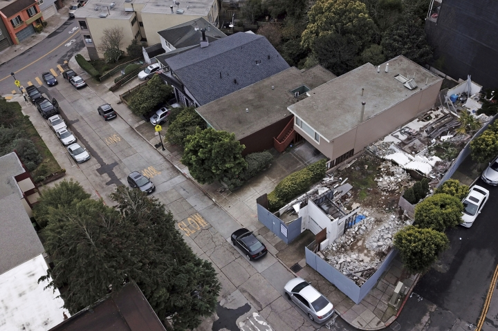 File - This Friday, Dec. 14, 2018, file photo, shows a demolished house, right, on a property in San Francisco. San Francisco officials reversed an order that would have forced a man who illegally demolished a San Francisco house designed by modernist architect Richard Neutra to rebuild the house exactly as it was. The city Planning Commission in December ordered Ross Johnston to rebuild the home and add a sidewalk plaque describing the home's origins, demolition and replication. The board reversed itself Thursday, Aug. 29, 2019, after a lawsuit by Johnson, instead approving a larger two-unit structure. (Santiago Mejia/San Francisco Chronicle via AP, File)