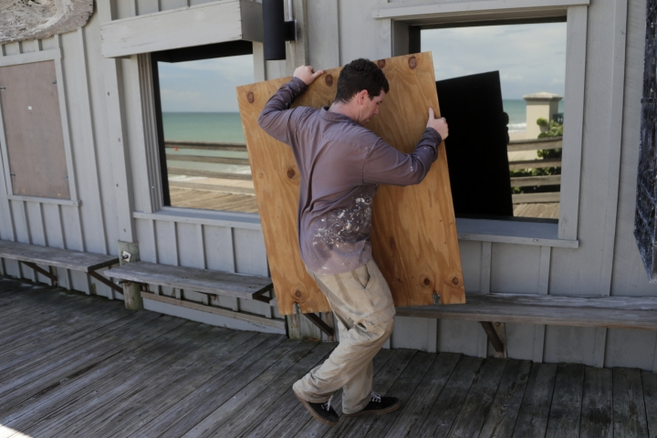 Lyle Fidgeon boards windows at the Ocean Grill in preparation for Hurricane Dorian, Friday, Aug. 30, 2019, in Vero Beach, Fla. The National Hurricane Center says Dorian could hit the Florida coast as a major hurricane. (AP Photo/Lynne Sladky)