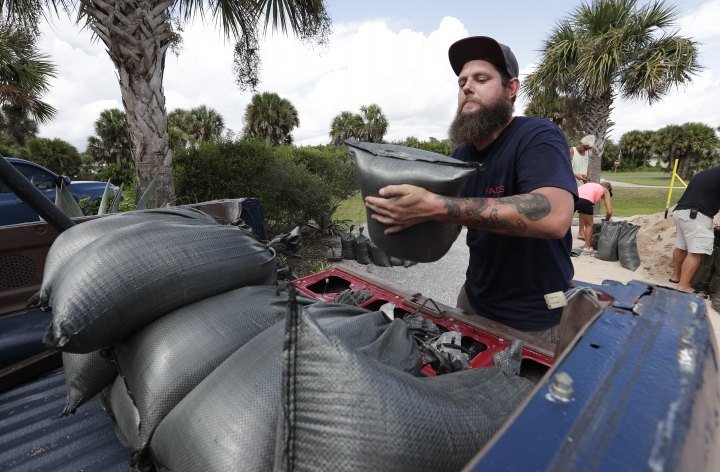 Matt Rohrer loads sandbags in the back of his vehicle for his home in preparation for Hurricane Dorian Friday, Aug. 30, 2019, in Flagler Beach, Fla. (AP Photo/John Raoux)