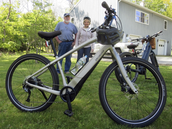 FILE-In this June 8, 2019 file photo, Gordon and Janice Goodwin show their electric-assist bicycles outside their home in Bar Harbor, Maine. Motorized electric bicycles may soon be humming their way into serene national parks and other public lands nationwide, under a new Trump administration order allowing the so-called e-bikes on every federal trail where a regular bike can go. (AP Photo/David Sharp, files)