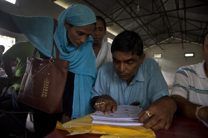 Villagers check their names in the final list of the National Register of Citizens (NRC) at an NRC center in Buraburi village, in Morigaon district, in the northeastern Indian stat of Assam, Saturday, Aug. 31, 2019. India has published the final citizenship list in the Indian state of Assam, excluding nearly two million people amid fears they could be rendered stateless. The list, known as the National Register of Citizens (NRC), intends to identify legal residents and weed out illegal immigrants from the state. (AP Photo/Anupam Nath)