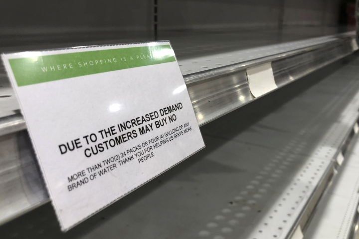 Empty shelves where water is sold at a grocery store are shown, Friday, Aug. 30, 2019, in North Miami, Fla. All of Florida is under a state of emergency and authorities are urging residents to stockpile a week's worth of food and supplies as Hurricane Dorian gathers strength and aims to slam the state as soon as Monday as a Category 4 storm. (AP Photo/Wilfredo Lee)