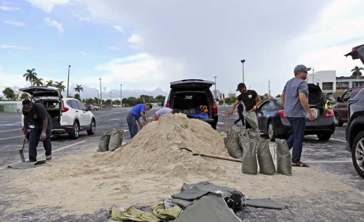 People fill sandbags at the parking of the Big Easy Casino, Friday, Aug. 30, 2019 in Hallandale Beach, Fla. Hurricane Dorian was muscling a chaotic path toward Florida, with officials and residents bracing for the possibility it would unleash its full fury early next week but clinging to the glimmer of hope that the strengthening storm could simply skirt the coastline. (David Santiago/Miami Herald via AP)