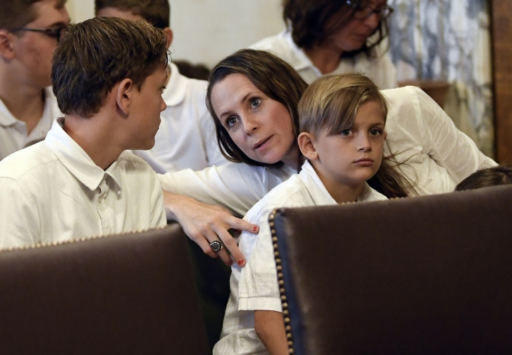 FILE - In this Aug. 14, 2019, file photo, Leslie Danesi, center, sits with her children Lorenzo Danesi, left, and Gabriel Danes, right, as attorneys prepare to speak at a hearing challenging the constitutionality of the state legislature's repeal of the religious exemption to vaccination in Albany, N.Y. Lawmakers did away with the religious exemption for vaccinations in June amid the nation's worst measles outbreak since 1992. Danesi said she views her children as gifts from God, and they should not be subject to forced injections. (AP Photo/Hans Pennink, File)