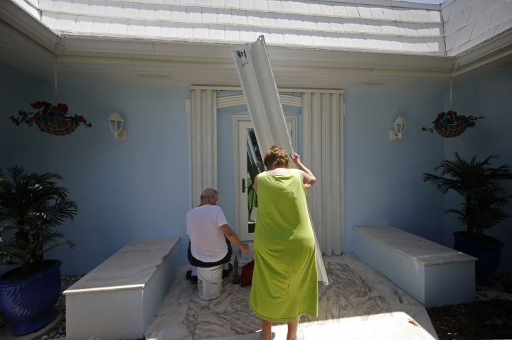 Jerry and Patricia Perkins shudder their home on the barrier island in Vero Beach, Fla., Sunday, Sept. 1, 2019, in preparation for the possibility of Hurricane Dorian making landfall. (AP Photo/Gerald Herbert)