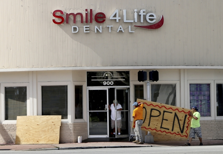 People at a business in the Normandy area in Miami Beach, Fla., remove the plywoods used as shutters covering the front windows Saturday, Aug. 31, 2019, as Hurricane Dorian's latest track shows the storm has shifted east and north, increasing the possibility that the storm would not make landfall in the state of Florida. (Pedro Portal/Miami Herald via AP)