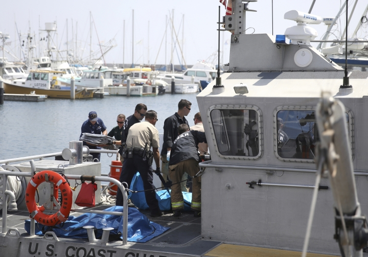 Santa Barbara City Search and Rescue along with Santa Barbara Sheriff officers move a recovered body on the dock at Santa Barbara Harbor in Santa Barbara, Calif., Monday, Sept. 2, 2019. The body was recovered from a dive boat fire near Santa Cruz Island early Monday. (AP Photo/Daniel Dreifuss)