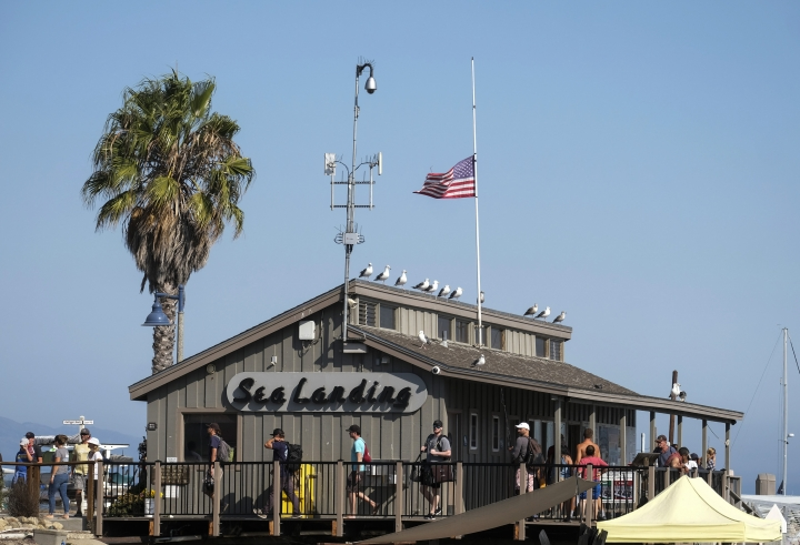 A U.S. flag flies at half-staff on the Sea Landing, where the Truth Aquatics office is situated, at Santa Barbara Harbor in Santa Barbara, Calif., Monday, Sept. 2, 2019. A boat carrying recreational scuba divers that caught a fire early Monday while anchored near Santa Cruz Island off the Southern California coast was owned and operated by Truth Aquatics. (AP Photo/Ringo H.W. Chiu)