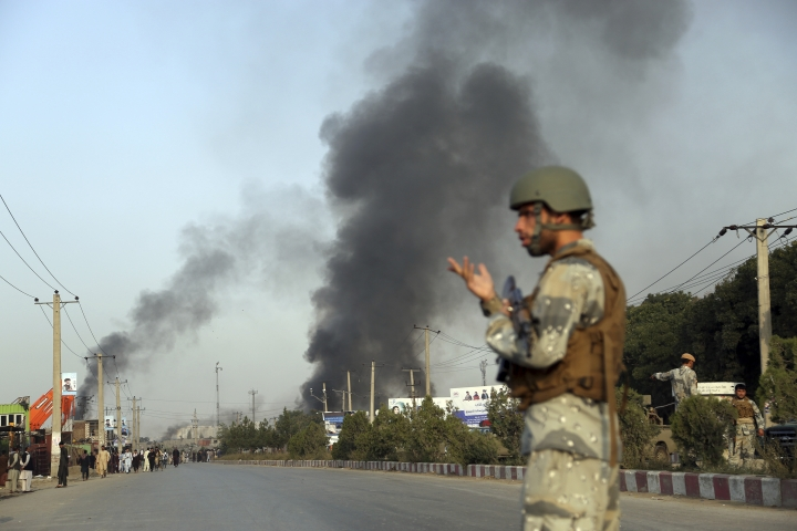 An Afghan police stands guard as smoke billows from the Green Village, home to several international organizations and guesthouses, in Kabul, Afghanistan, Tuesday, Sept. 3, 2019. Angry residents climbed into the international compound that had been targeted and set part of it on fire. (AP Photo/Rahmat Gul)