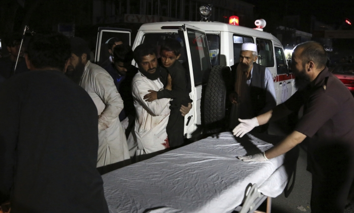 Afghan men carry an injured young boy into a hospital after a large explosion in Kabul, Afghanistan, Monday, Sept. 2, 2019. Afghan officials say a large explosion in Kabul has targeted the Green Village compound, home to several international organizations and guesthouses. (AP Photo/Rahmat Gul)