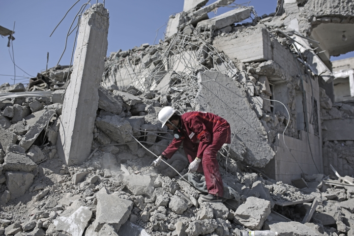 A rescue worker uncovers the body of a detainee from under the rubble of a Houthi-held detention center destroyed by Saudi-led airstrikes in Dhamar, Yemen, Sunday, Sept. 1, 2019. Yemeni officials say airstrikes by the Saudi-led coalition hit a detention center in the southwestern Dhamar province, killing at least 60 people. The officials say the airstrikes took place Sunday and targeted a college in the city of Dhamar, which the Houthi rebels use as a detention center. (AP Photo/Hani Mohammed)