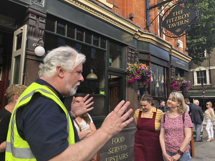 In this July 13, 2019, photo, writer and tour guide Nick Hennegan leads a group of tourists through London's Fitzrovia area to explore pubs connected to famous writers. The London Literary Pub Crawl allows visitors to experience a playful and IPA-fueled tour unlocks stories linked to London locations where renowned novelists and poets drank and debated literature. (AP Photo/Russell Contreras)