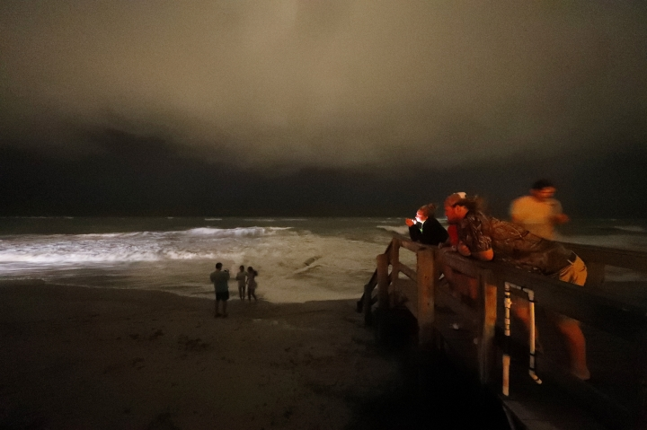 "People stand on the boardwalk along the Atlantic Ocean at night as the outer bands of Hurricane Dorian reach Vero Beach, Fla., Monday, Sept. 2, 2019. The National Hurricane Center extended watches and warnings across the Florida and Georgia coasts Monday. Forecasters expected Dorian to stay off shore, but meteorologist Daniel Brown cautioned that ""only a small deviation"" could draw the storm's dangerous core toward land. (AP Photo/Gerald Herbert)"