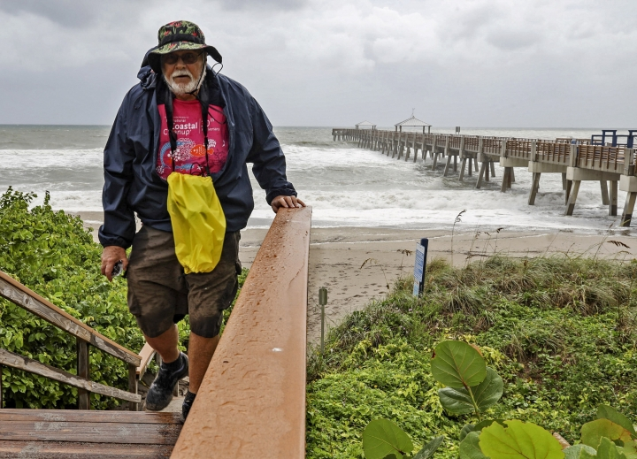 A beach goer climbs the stairs near the Juno Beach Pier as Hurricane Dorian crawls toward Florida while the storm continues to ravage the Bahamas on Monday, Sept. 2, 2019. (Carl Juste/Miami Herald via AP)