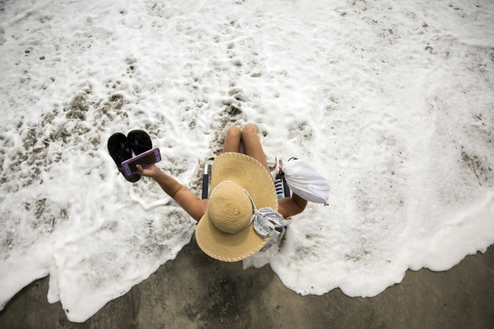 Resident and business owner Karen Kelly takes some time off to experience the heavy surf in advance of Hurricane Dorian, Tuesday, Sept. 3, 2019, in Tybee Island, Ga. The state issued a mandatory evacuation along the coast of Georgia on Sunday well before the storm's expected arrival. (AP Photo/Stephen B. Morton)