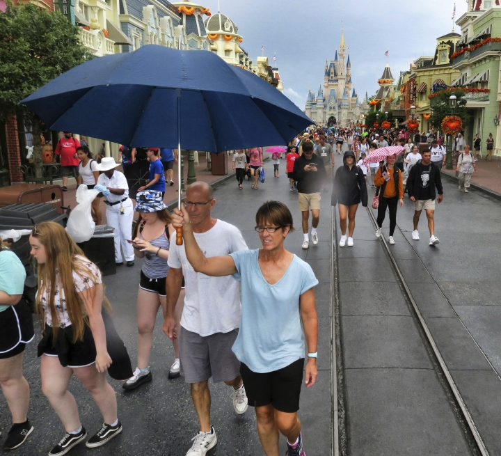 Guests leave the Magic Kingdom at Walt Disney World Tuesday, Sept. 3, 2019, in Lake Buena Vista, Fla., after the park closed early due to weather spawned by Hurricane Dorian. (Joe Burbank/Orlando Sentinel via AP)