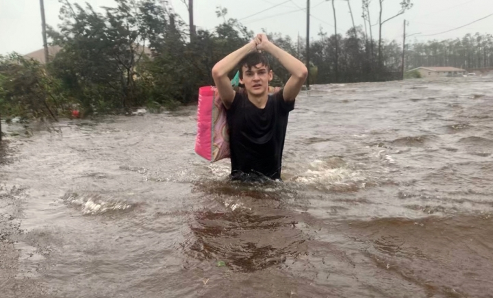 Matthew Aylen wades through waist deep water as he is rescued from his flooded home during Hurricane Dorian in Freeport, Bahamas, Tuesday, Sept. 3, 2019. Practically parking over the Bahamas for a day and a half, Dorian pounded away at the islands Tuesday in a watery onslaught that devastated thousands of homes, trapped people in attics and crippled hospitals. Matthew Aylen is the son of Photojournalist Tim Aylen, author of this photo. (AP Photo/Tim Aylen)