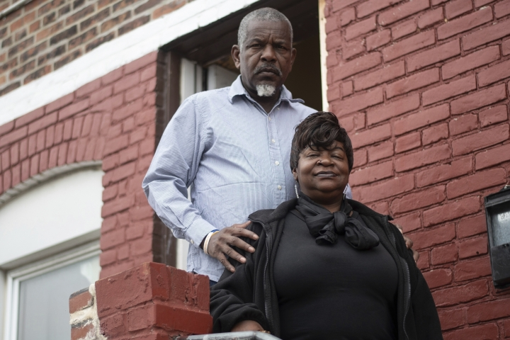 In this June 13, 2019 photo, Michael Thomas and Alberta Wilkerson stand on the front steps of their home in the Broadway East neighborhood of Baltimore. The couple's home has no air conditioning and both have health conditions that are made worse by the summer's heat. (University of Maryland Capital News Service via AP)