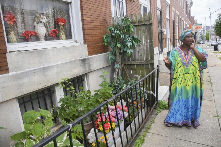 In this July 9, 2019 photo, Lorraine Diggs stands on the sidewalk outside her rowhouse in East Baltimore. Diggs is passionate about maintaining the trees outside of her home and has dedicated a small garden in front of her house to her late mother. (University of Maryland Capital News Service via AP)