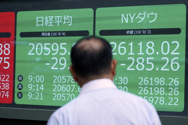 A man looks at an electronic stock board showing Japan's Nikkei 225 index and New York Dow Jones index at a securities firm in Tokyo Wednesday, Sept. 4, 2019. Asian stock markets rose Wednesday following surprise weakness in U.S. manufacturing and wrangling in Britain over the country's departure from the European Union. (AP Photo/Eugene Hoshiko)
