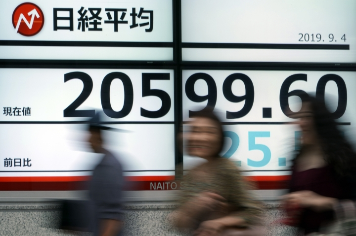 People walk past an electronic stock board showing Japan's Nikkei 225 index at a securities firm in Tokyo Wednesday, Sept. 4, 2019. Asian stock markets rose Wednesday following surprise weakness in U.S. manufacturing and wrangling in Britain over the country's departure from the European Union. (AP Photo/Eugene Hoshiko)
