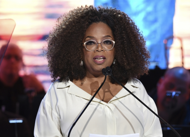 "FILE - In this May 15, 2019 file photo, Oprah Winfrey speaks at the Statue of Liberty Museum opening celebration at Battery Park in New York. Winfrey announced Wednesday, Sept. 4, 2019, that she will embark on a nine city arena tour called ""Oprah's 2020 Vision: Your Life in Focus,"" that will focus on maintaining a healthy lifestyle. The tour will begin Jan. 4, 2020 in Fort Lauderdale, Fla., and end in early March in Denver. (Photo by Evan Agostini/Invision/AP, File)"