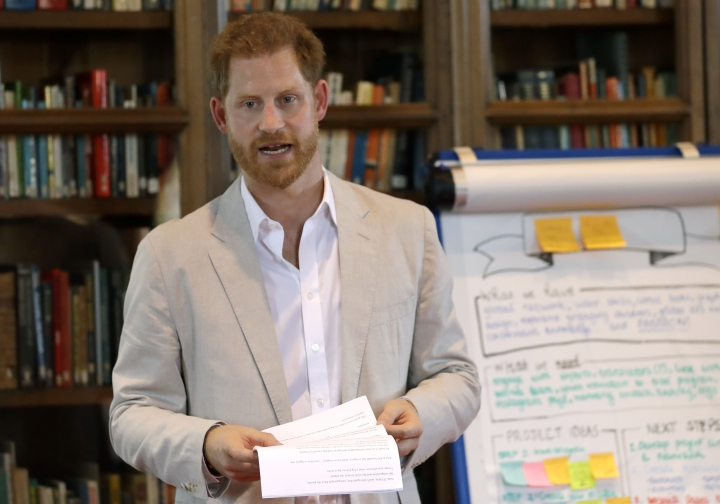 FILE - In this July 23, 2019 file photo, Britain's Prince Harry delivers a speech as he attends Dr Jane Goodall's Roots & Shoots Global Leadership Meeting at St. George's House, Windsor Castle in England. The eco-minded Prince Harry announces a massive travel sustainability initiative in partnership with key service providers that's aimed at bettering the practices of the global industry amid an ever-increasing number of travelers. The Duke of Sussex announced Travalyst at a news conference Tuesday, Sept. 3, in Amsterdam, a city hit hard by over-tourism. He was joined by his partners, including Visa, TripAdvisor and Booking.com.(AP Photo/Kirsty Wigglesworth, Pool)