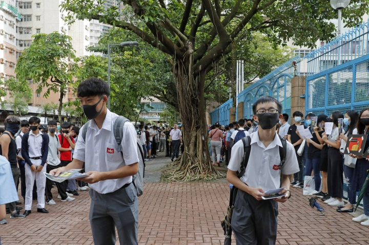 High school students wearing masks, deliver leaflets to support the school boycott, in Hong Kong, Wednesday, Sept. 4, 2019. Hong Kong leader Carrie Lam said Tuesday she has never tendered her resignation to China over the anti-government protests that have roiled the city for three months. (AP Photo/Kin Cheung)