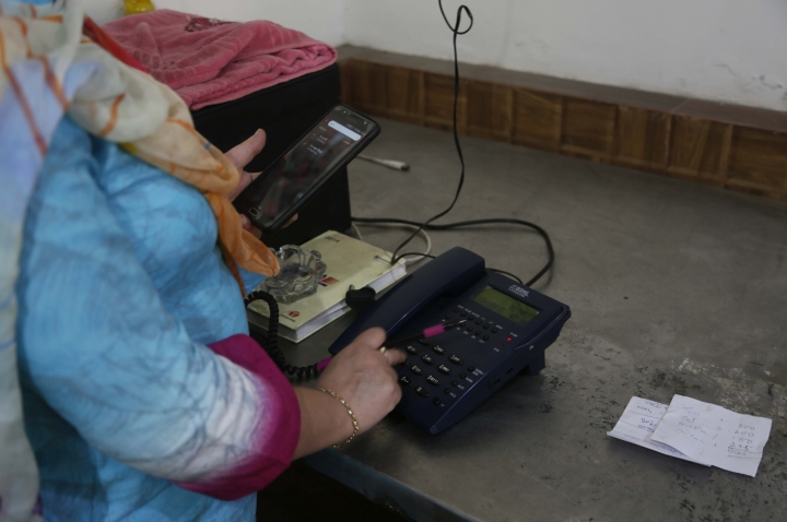 A Kashmiri woman makes a call to a relative after landline phones were restored in Srinagar, Indian controlled Kashmir, Thursday, Sept. 5, 2019. Indian authorities say they have restored all landline phones in the Himalayan region of Kashmir after communication services, including mobile Internet, were suspended on Aug. 5, when India's Hindu-nationalist government revoked the disputed Muslim-majority region's special constitutional status and put the region under strict security lockdown. (AP Photo/Mukhtar Khan)