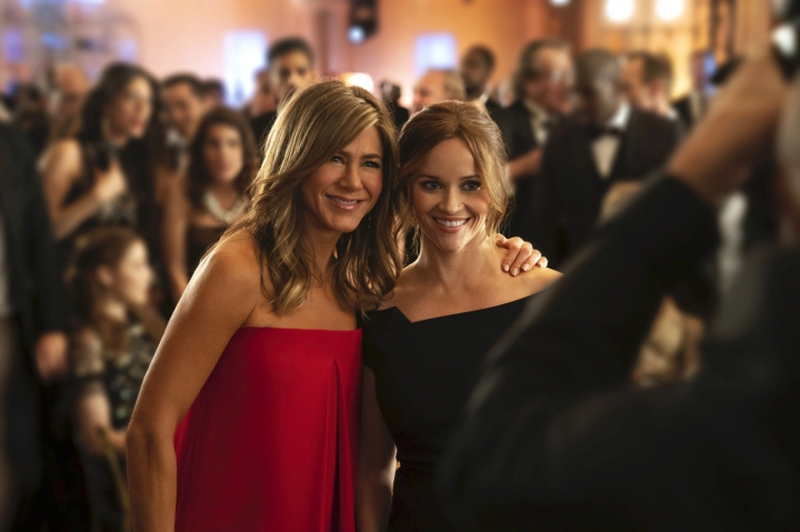 """This image released by Apple TV Plus, Jennifer Aniston, left, and Reese Witherspoon appear in a scene from """"The Morning Show,"""" behind-the-scenes look at fictional players in the competitive morning broadcast realm. (Apple TV Plus via AP)"""