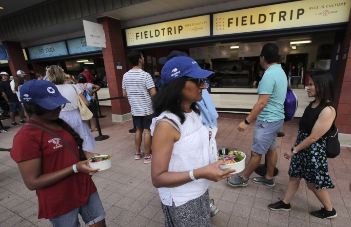 This Aug. 30, 2019 photo shows tennis fans with rice bowls from the Field Trip counter-service restaurant kiosk on the food court at the US Open tennis championships in New York. Chef JJ Johnson named the restaurant Field Trip based on all the trips he's taken globally. (AP Photo/Charles Krupa)