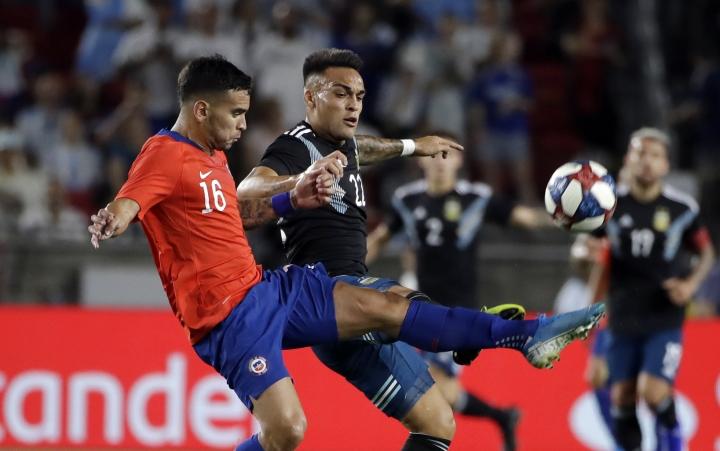 Chile's Sebastian Vegas, left, works against Argentina's Lautaro Martinez during the first half of an international friendly soccer match Thursday, Sept. 5, 2019, in Los Angeles. (AP Photo/Marcio Jose Sanchez)