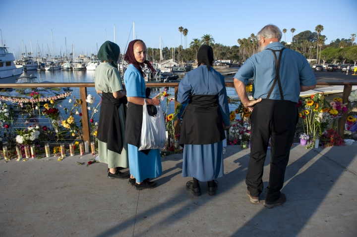 A family from Iowa observes a memorial placed for the victims of Monday's dive boat fire at the Santa Barbara Harbor on Wednesday, Sept. 4, 2019, in Santa Barbara, Calif. (AP Photo/Christian Monterrosa )