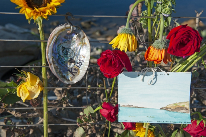 Flowers and handmade art on an abalone shell is displayed at a memorial for the victims of Monday's dive boat fire at the Santa Barbara Harbor on Wednesday, Sept. 4, 2019, in Santa Barbara, Calif. (AP Photo/Christian Monterrosa )