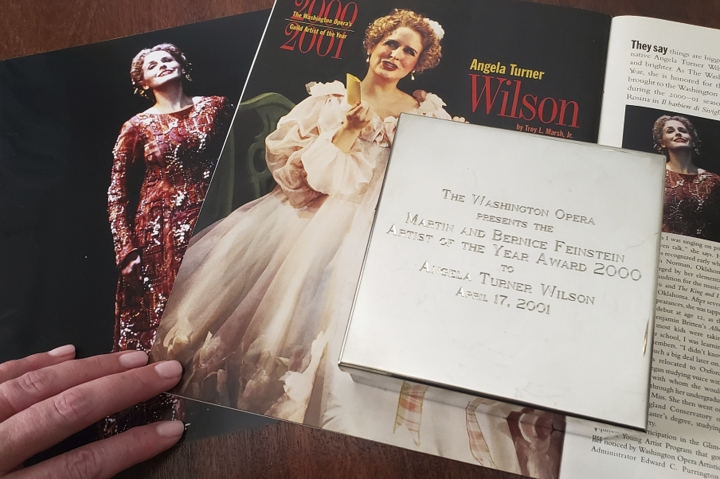 """In this Tuesday, Sept. 2, 2019 photo provided by opera singer Angela TurnerWilson, she displays her 2000 Artist of the Year award from the Washington Opera next to a photo of herself from a 1999 performance of """"Le Cid,"""" left, and a magazine article in a Washington Opera magazine, at her home in Texas. An evening before a performance of """"Le Cid,"""" part of the Washington Opera's 1999-2000 season, she said she and Placido Domingo were having their makeup done together when he rose from his chair, stood behind her and put his hands on her shoulders. As she looked at him in the mirror, he suddenly slipped his hands under her bra straps, she said, then reached down into her robe and grabbed her bare breast. """"It hurt,"""" she told The Associated Press. """"It was not gentle. He groped me hard."""" She said Domingo then turned and walked away, leaving her stunned and humiliated. (CourtesyAngela TurnerWilsonvia AP)"""