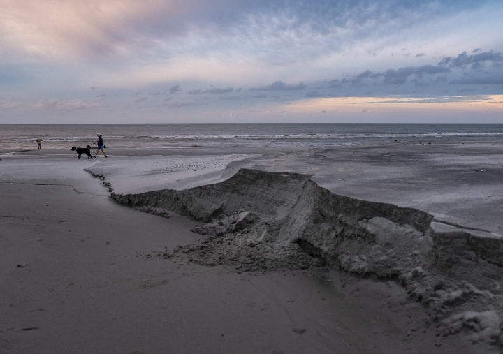 A woman walks her dog at sunrise past beach erosion caused by Hurricane Dorian in the Cherry Grove section of North Myrtle Beach, S.C., Friday, Sept. 6, 2019. Residents of Horry County breathed a collective sigh of relief today after Hurricane Dorian passed with only minor damages.(Jason Lee/The Sun News via AP)