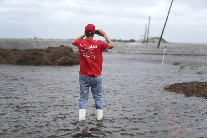 Mike Rogers takes a photo of the storm surge from Hurricane Dorian that blocks Cedar Island off from the mainland on NC 12 in Atlantic, N.C., after Hurricane Dorian past the coast on Friday, Sept. 6, 2019. (AP Photo/Tom Copeland)