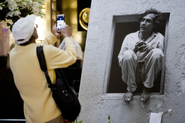 A man takes a photo of a photograph of the late Mexican painter Francisco Toledo during a memorial at the Bellas Artes Palace in Mexico City, Friday, Sept. 6, 2019. Toledo, who was well-known and respected in Mexico both for his art and his activism, has died, the country's president announced late Thursday. (AP Photo/Eduardo Verdugo)