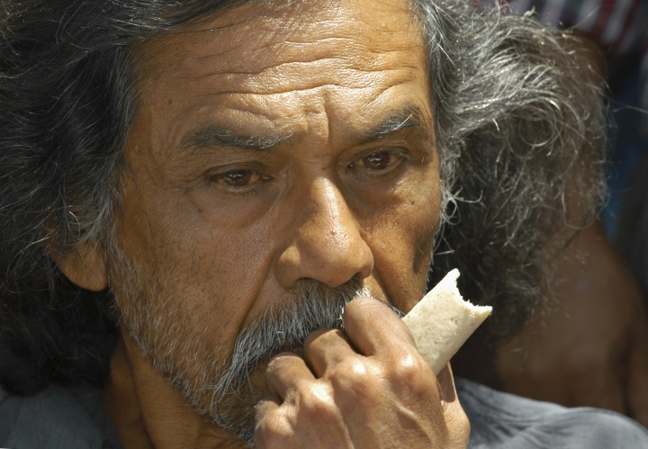 FILE - In this March 11, 2004 file photo, Francisco Toledo, one of Mexico's most prominent painters, eats a corn tortilla in the city center of Oaxaca, Mexico, to protest the presence of genetically modified corn in the Mexican wild. The family of Toledo has announced on Thursday, September 5, 2019, the he has died. (AP Photo/Marco Ugarte, File)