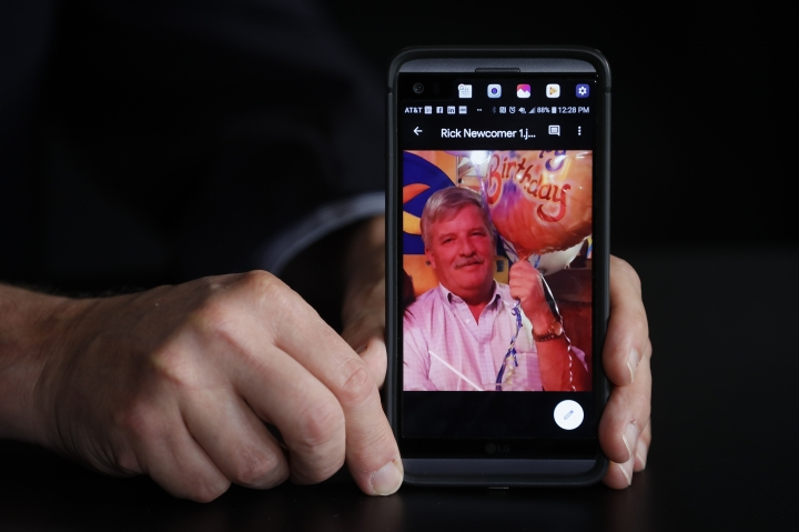 Larry Newcomer holds an image of his older brother Richard during an interview with The Associated Press, Monday, Aug. 26, 2019, in Cincinnati. Newcomer's older brother Richard was killed during a shooting in downtown Cincinnati on Sept. 6, 2018. Also killed were Prudhvi Raj Kandepi, 25, a Fifth Third consultant, and Luis Felipe Calderon, 48, a Fifth Third employee. (AP Photo/John Minchillo)