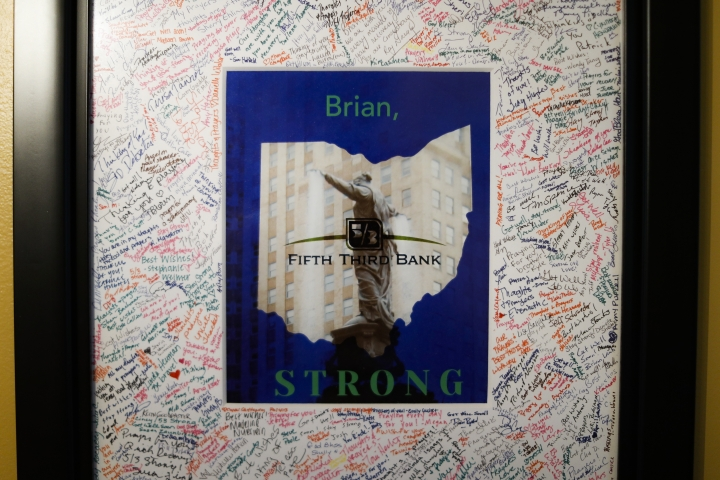 A frame matte covered in signatures and well-wishes from Fifth This Bank employees hands at the home of Brian Sarver, Tuesday, Aug. 27, 2019, in Lebanon, Ohio. People caught in the middle of a downtown building shooting in Cincinnati one year ago Thursday say they struggle with frequent reminders that trigger bad memories. Sarver was shot at close range, often wonder why they escaped death that day. (AP Photo/John Minchillo)