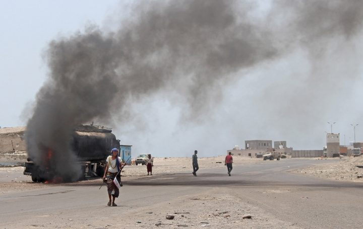 FILE - In this Aug. 30, 2019 file photo, people inspect an oil tanker truck set ablaze during recent clashes between Yemeni southern separatists and government forces in near Aden, Yemen. Fighting between their allies in southern Yemen has opened a gaping wound in the Saudi Arabia and the United Arab Emirates' coalition fighting the country's rebels. If they can't fix it, it threatens to further fragment the country into smaller warring pieces. (AP Photo/Wail al-Qubaty, File)